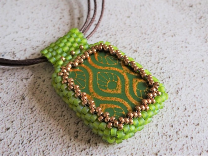 Polymer clay focal bead with beaded bezel