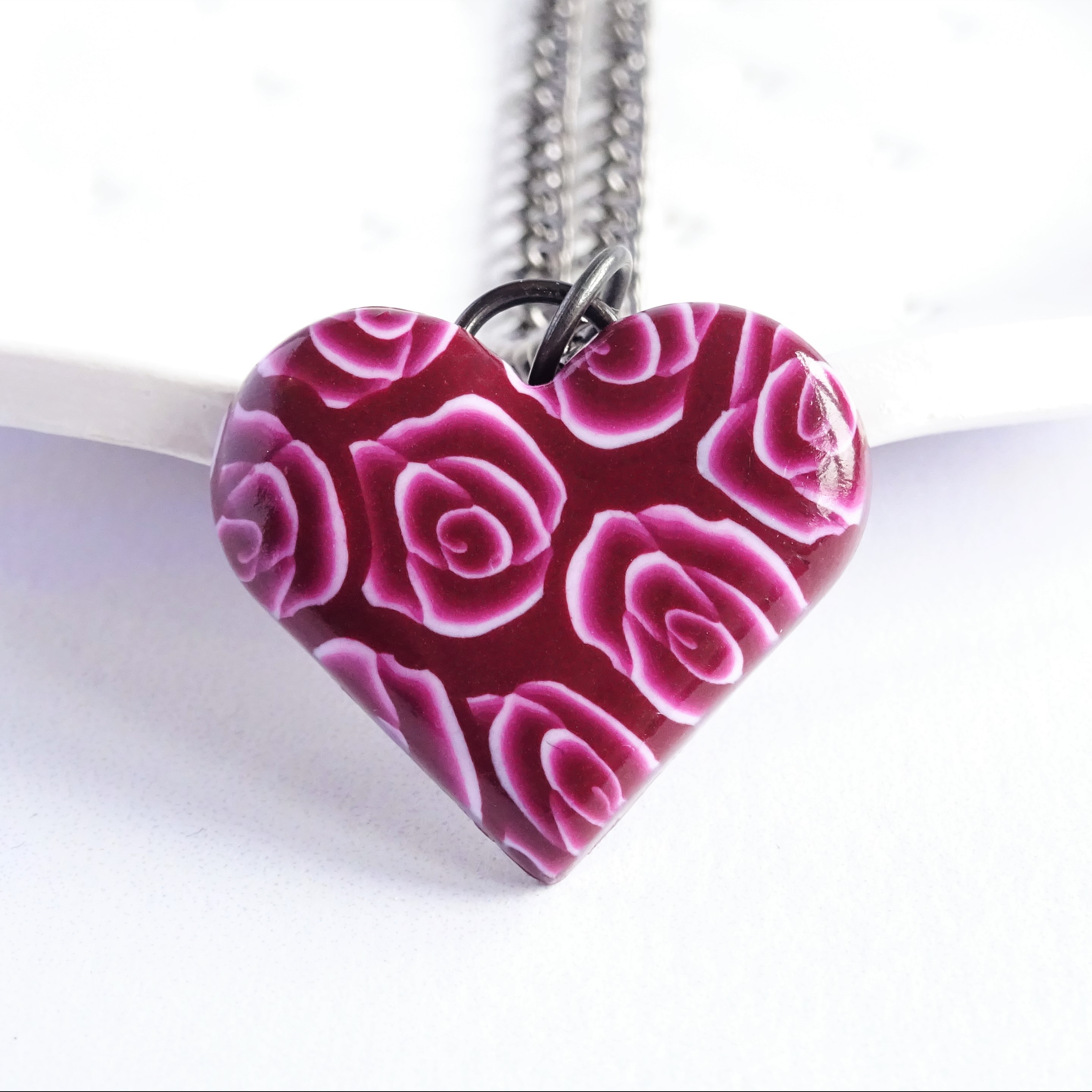 A red heart rose pendant on a long black chain