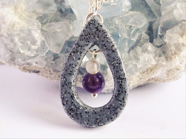 A teardrop necklace with amethyst beads